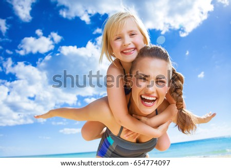 Sun kissed beauty. Portrait of happy young mother and child in swimwear on the beach having fun time