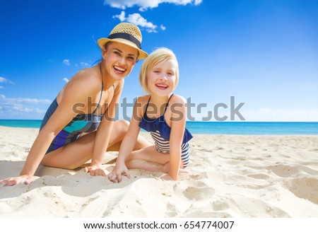 Sun kissed beauty. Portrait of smiling young mother and daughter in swimwear on the seacoast