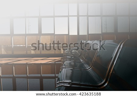 Sun light in window of blurred background space, Hospital waiting room with empty blue chairs. - stock photo