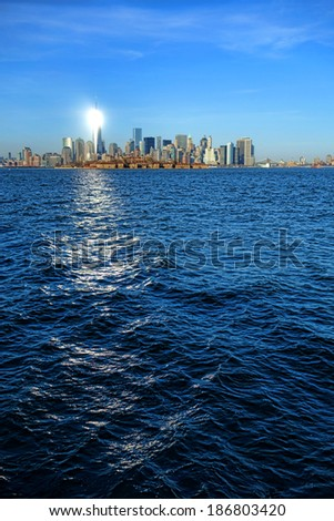 Sun light reflection shining like lighthouse beacon on gleaming surface of newest One World Trade Center Freedom Tower in New York City Downtown Lower Manhattan skyline cityscape on the Hudson River - stock photo