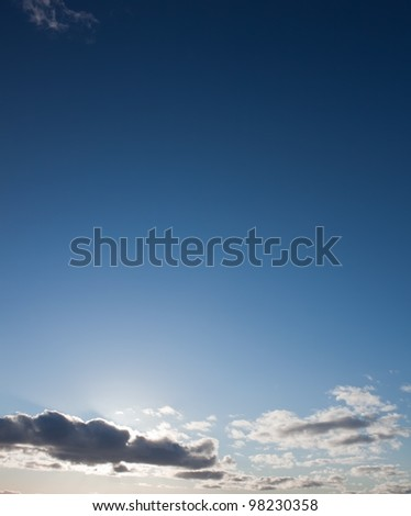Sun lights on the blue sky with big clouds - stock photo
