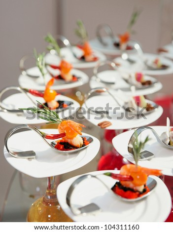 Sun-lit seafood snacks in plate - stock photo