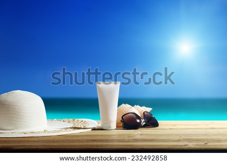 Sun lotion and sunglasses on the beach - stock photo