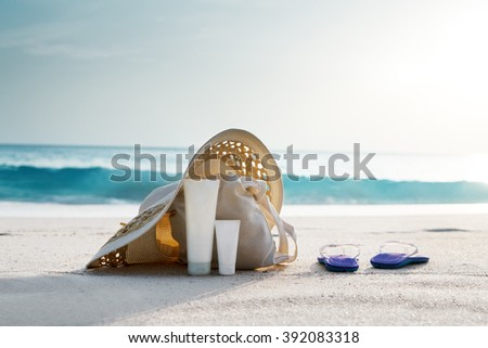 Sun lotion, hat  with bag at the tropical beach - stock photo