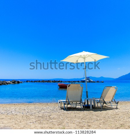 Sun Lounger and Parasol on a Beach - stock photo
