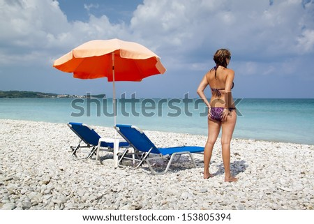 Sun lounger and umbrella on empty rock beach with beautiful girl - stock photo