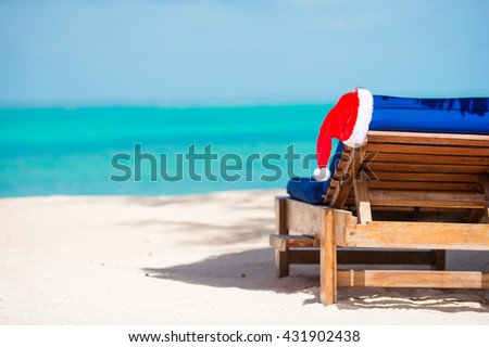 Sun lounger with Santa hat at beautiful tropical beach with white sand and turquoise water