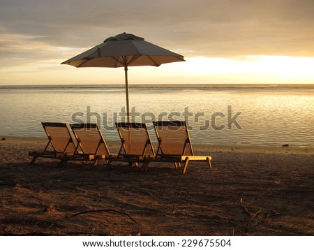 Sun loungers and parasols on a sandy beach at sunset - stock photo