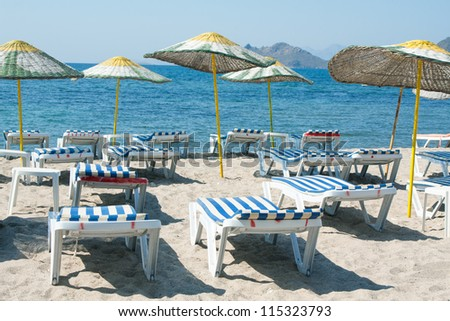 Sun loungers and wicker parasols on sandy beach in Turgutreis in the Bodrum Peninsula, Turkey.