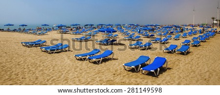 Sun loungers on beach waiting for tourists sunbathing for a sun tan, as sea mist clears to blue skies. - stock photo