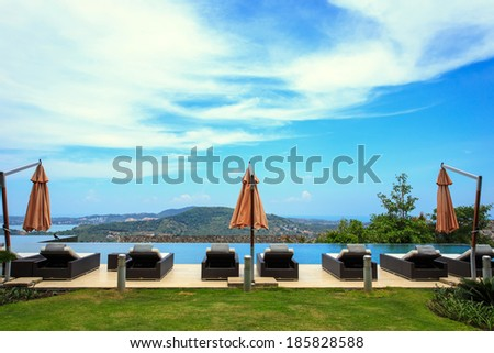 sun loungers stand at the pool and beautiful view - stock photo