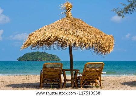 Sun loungers with an umbrella on the beach - stock photo