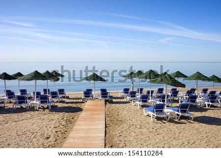 Sun loungers with umbrellas on a sandy beach by the Mediterranean Sea at the popular resort of Marbella in Spain,  Costa del Sol, Andalusia, Malaga province.