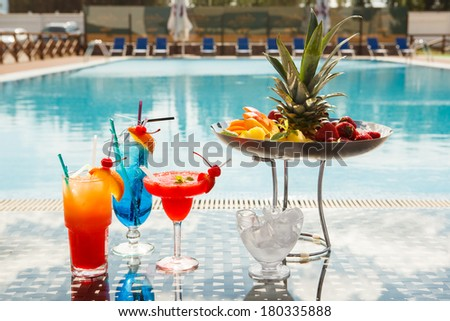 Sun lounges and cocktails by the pool - stock photo