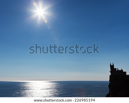 sun over Black Sea and Aurora cliff with Swallow Nest castle on South Coast of Crimea - stock photo