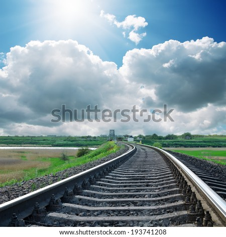 sun over clouds and railroad