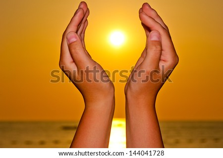 Sun over the sea in female hands - stock photo