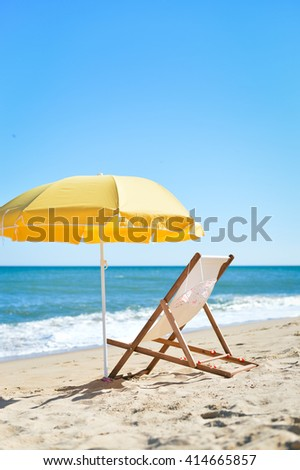Sun parasol, chair lounge and female hat on vacation beach sun shine outdoors