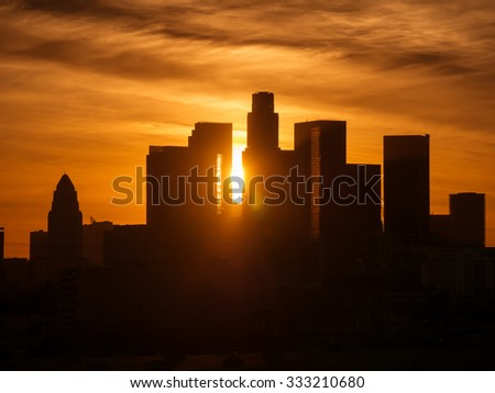Sun peeking between buildings of downtown Los Angeles skyline at sunset. - stock photo