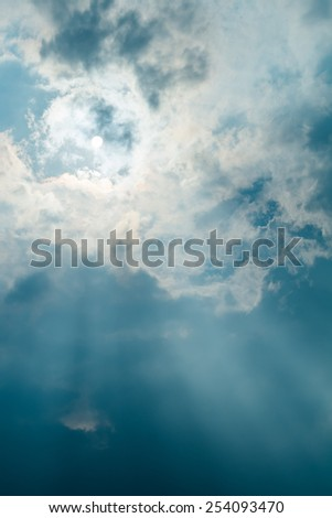 Sun projecting rays behind dramatic clouds in the blue sky before a thunderstorm - stock photo