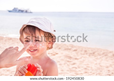 Sun protection. Hand of caucasian mother applying suncream  (suntan lotion) from a plastic container to her happy son before tanning during summer holiday on beach.  Copyspace, close up. - stock photo