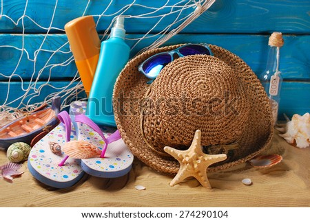 sun protection still life with straw hat,sunglasses,flip-flops and suntan lotion bottles on the beach  - stock photo