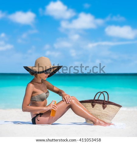 Sun protection uv rays skincare. Sunscreen spray bottle woman applying body lotion on smooth legs. Girl tanning putting sunblock Beach essentials for summer holidays: straw hat, sunglasses, tote bag. - stock photo