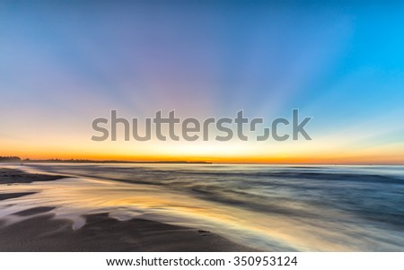Sun ray on beach in morning with red light from horizon and waves lapping at shore make morning more beautiful. Photos do background - stock photo