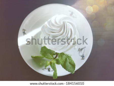 Sun rays and glare falling on delicate meringues, decorated with mint leaves on a platter. Vintage style. - stock photo