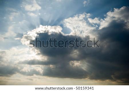 Sun rays blast trough the clouds - stock photo