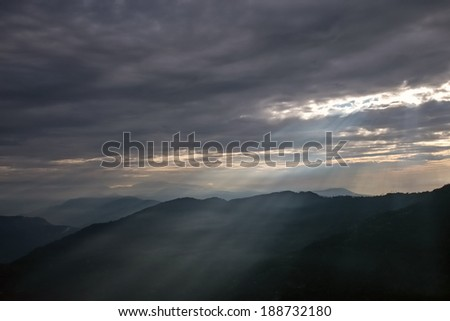 Sun rays breaking through dark clouds over mountains. Darjeeling, Himalayas, India - stock photo