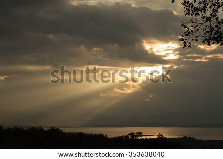Sun rays during sunrise over the moutain and lake, Thailand (Silhouette image) - stock photo