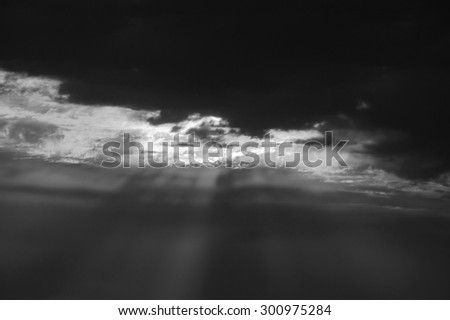 Sun rays glowing through the clouds. Dramatic lighting before a storm. Apocalypse concept. Aged photo. Black and white. - stock photo
