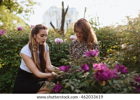 Sun rays highlight the trod in the forest. Attractive shapely dames are playing in the garden with flowers and hands...