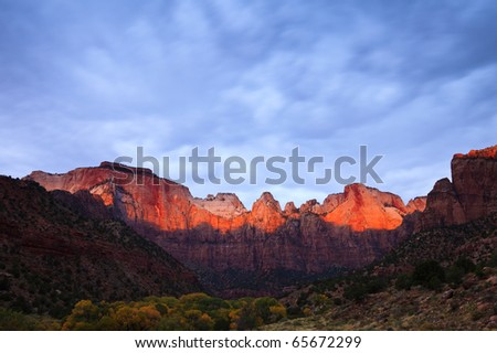 Sun rays hitting the top of Towers of the Virgin in Zion Canyon National Park, Utah. - stock photo