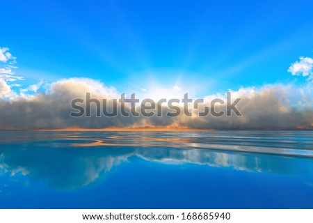 sun rays in clouds over tranquil ocean sunset - stock photo