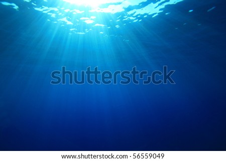 Sun rays in the blue ocean - stock photo