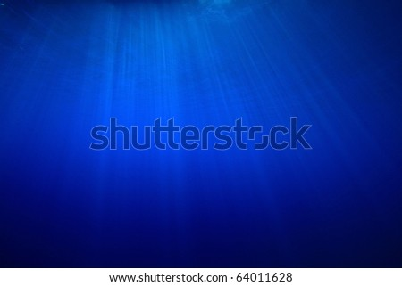 Sun rays in the blue sea - stock photo