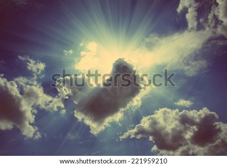 sun rays on dramatic sky wth clouds - vintage retro style - stock photo