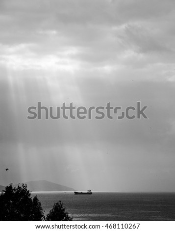 Sun rays over a ship in a sea, black and white
