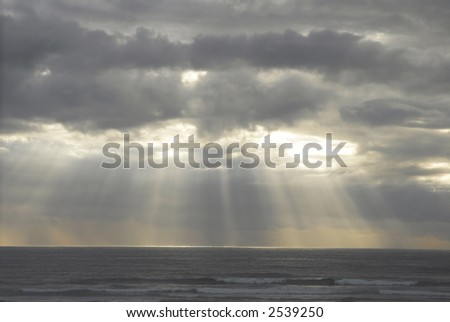 Sun rays over the ocean - stock photo