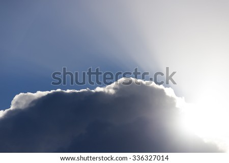 sun rays peering through the edge of a big fluffy cloud - stock photo