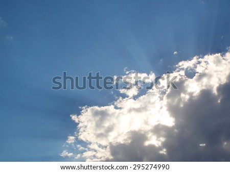 Sun Rays Shining from Behind Gray and White Clouds - stock photo
