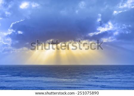 sun rays streaming through the storm clouds on the Irish wild Atlantic way - stock photo