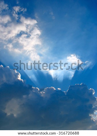 Sun rays striking through the clouds - stock photo
