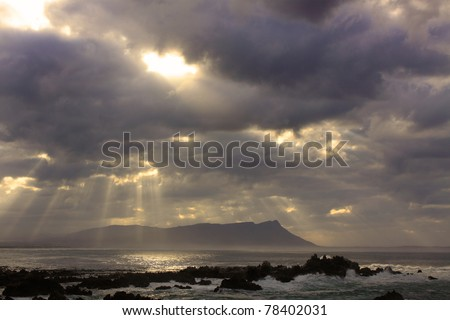 Sun rays through thick cloud cover over ocean - stock photo
