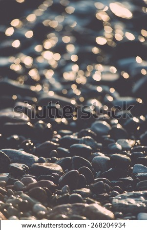sun reflections on Stones on the beach and sea water in sunset light - retro vintage film effect - stock photo