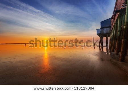 Sun rises and lights the Old Orchard Beach, Maine, pier - stock photo