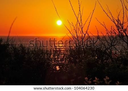 Sun rises over the ocean on Cape Cod - stock photo