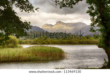 Sun rising and illuminating Langdale Pikes with Elter Water in foreground - stock photo